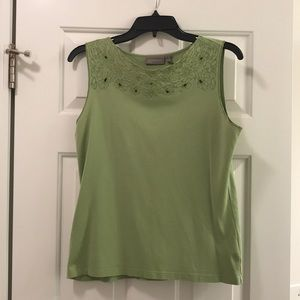 Green top with floral accents and eyelet holes